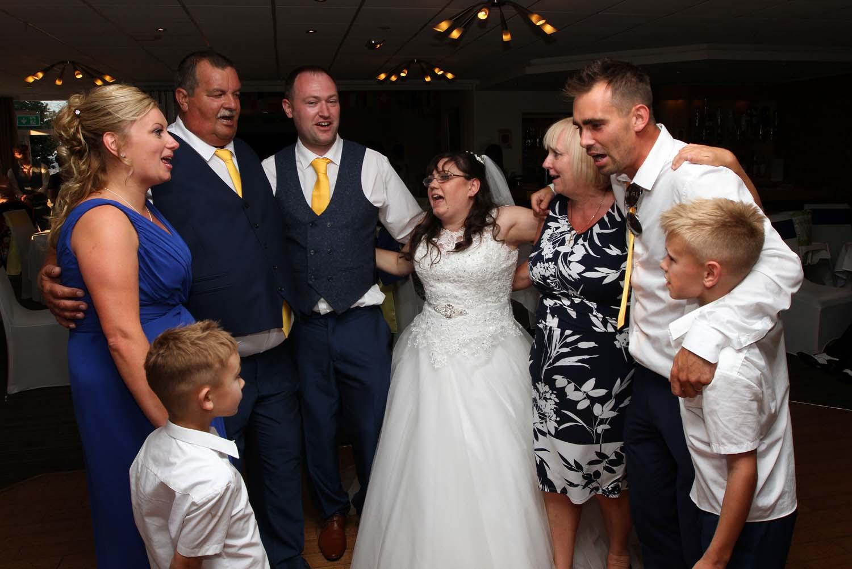 A wedding couple enjoying a sing along with heir family on the dancefloor