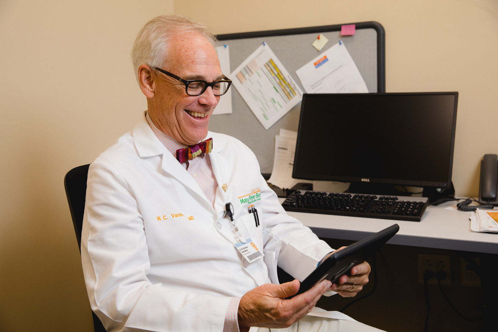 A doctor communicates virtually with a patient via webcam.