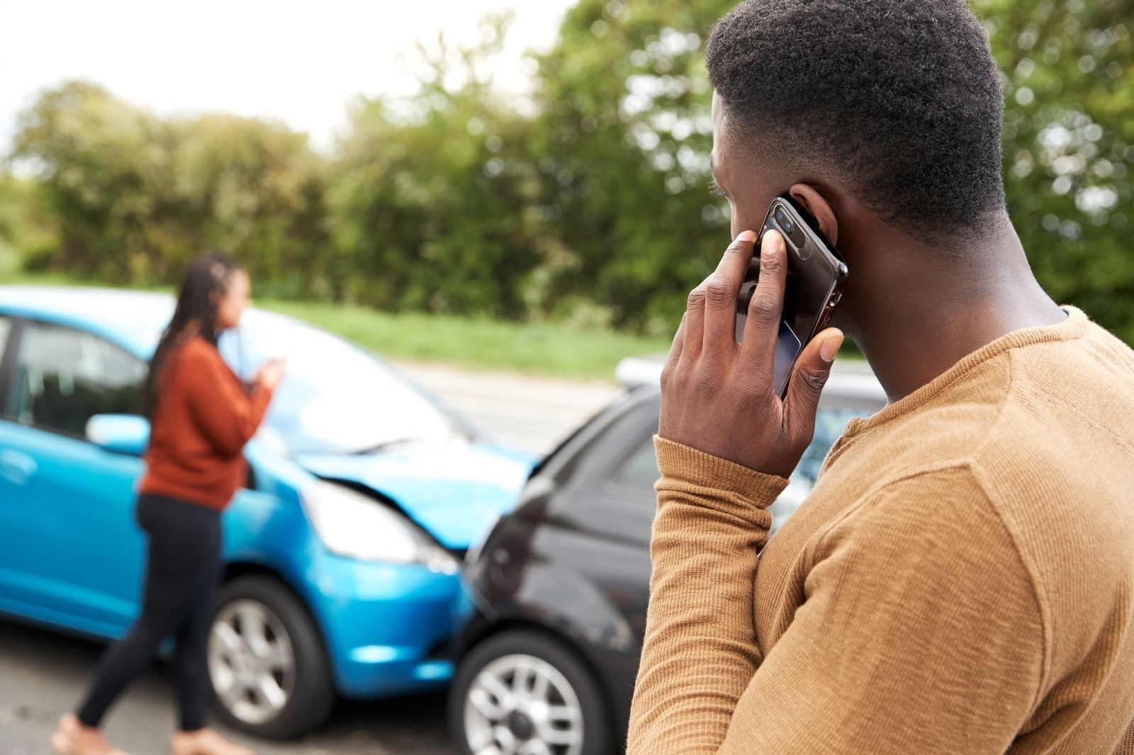 Man talking on phone at car accident