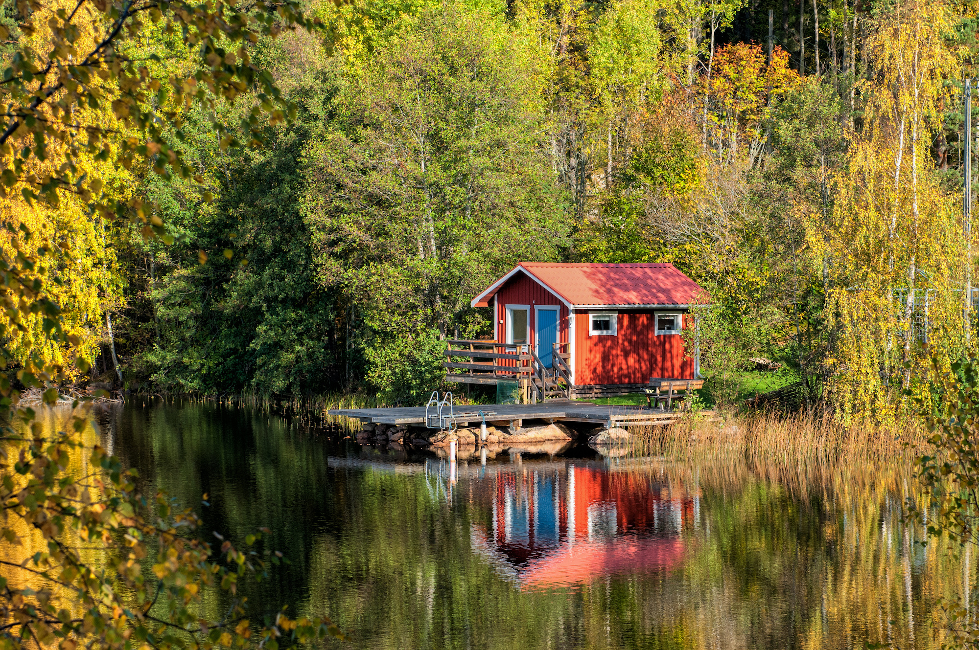 Cottage on lake with colourful trees