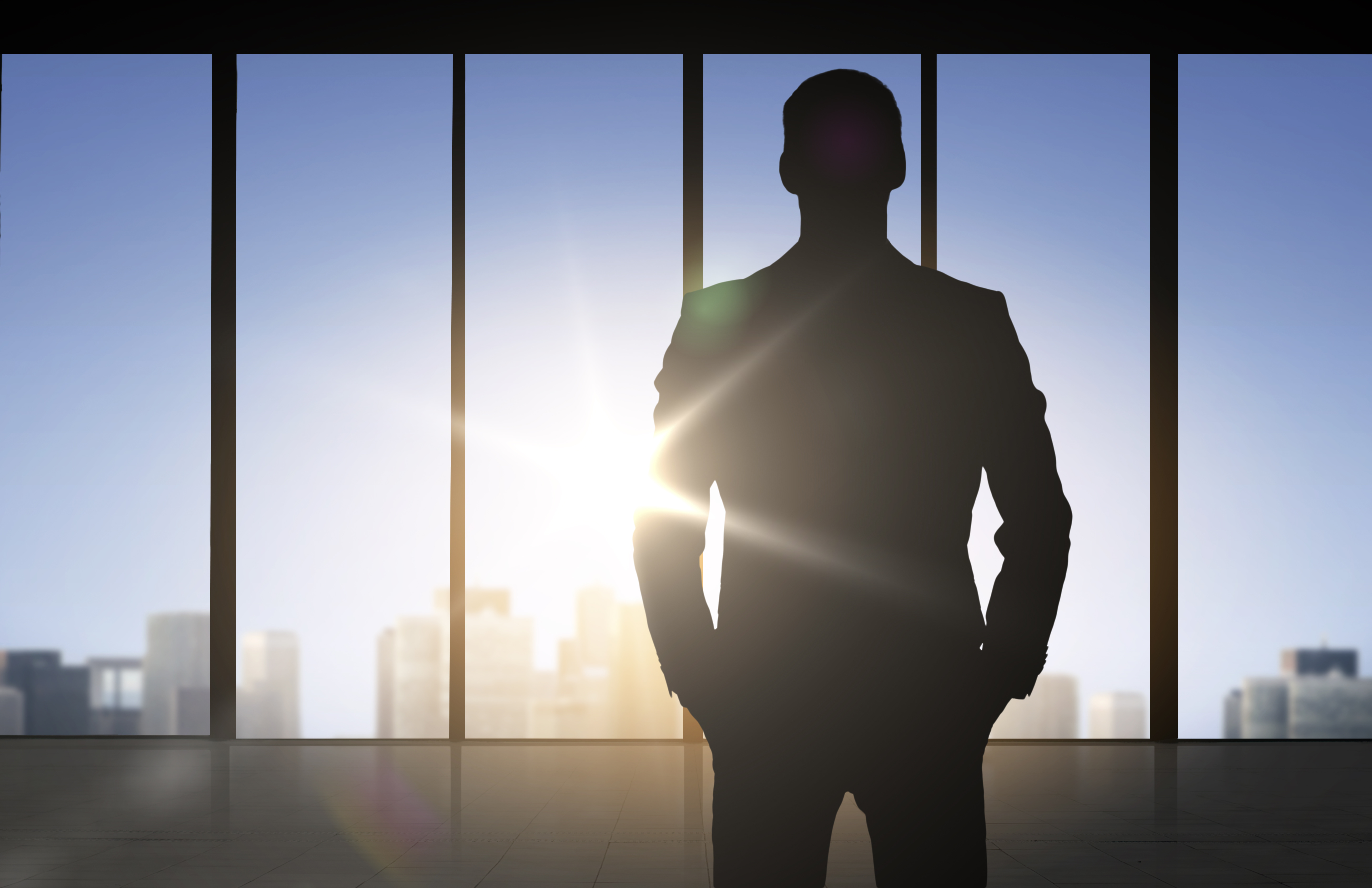 Man standing in office building looking out window.