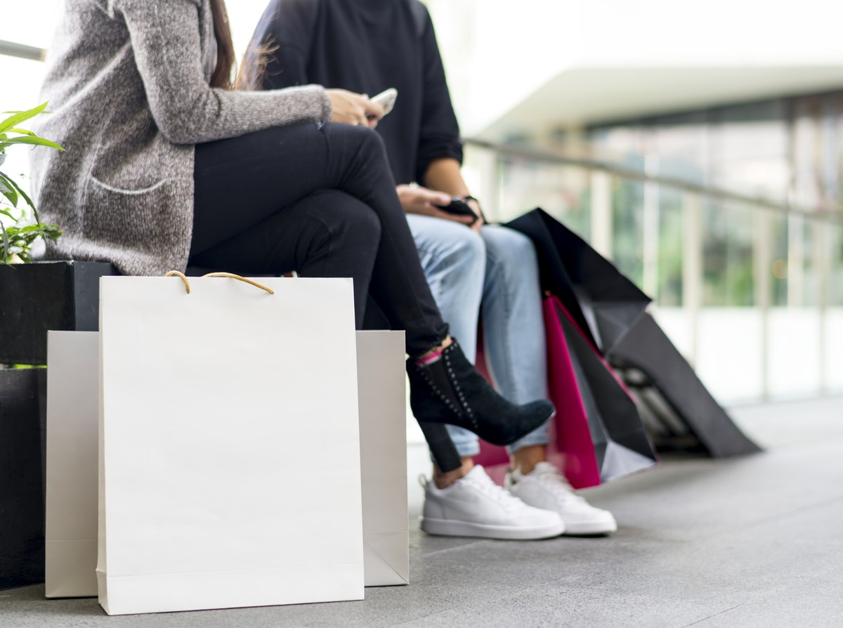 two people sitting on a bench with shopping bags