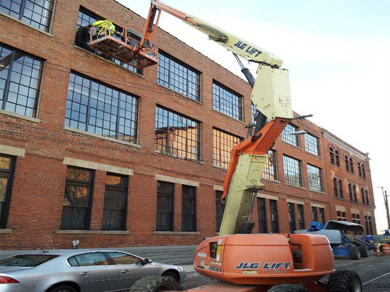 Using a crane to make hard to reach commercial windows shine.