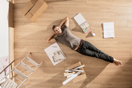 guy laying on floor surrounded by floor plans