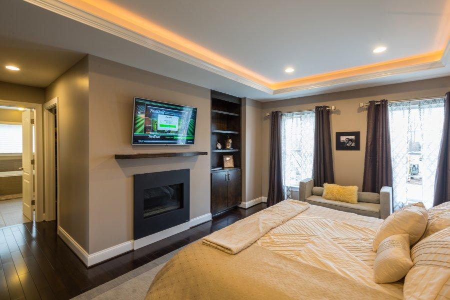 warm bedroom with fireplace below tv