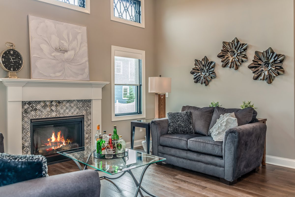 fireplace in tall ceiling room with grey couches