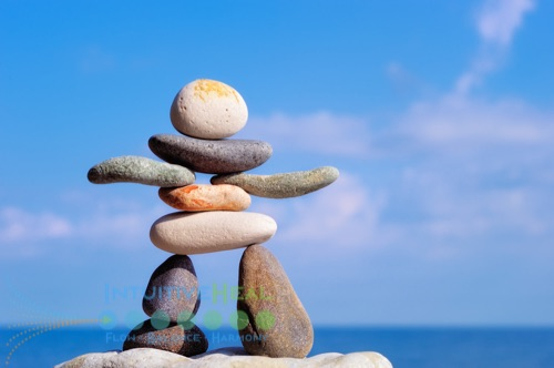 Photo of a rocks stacked in the form of a person against a sky and cloud background