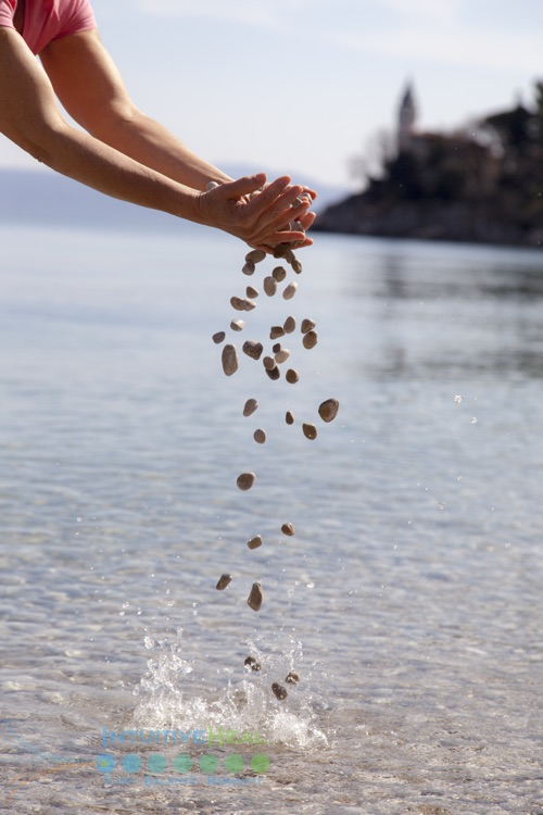 Photo of cupped hands dropping pebbles into a body of water