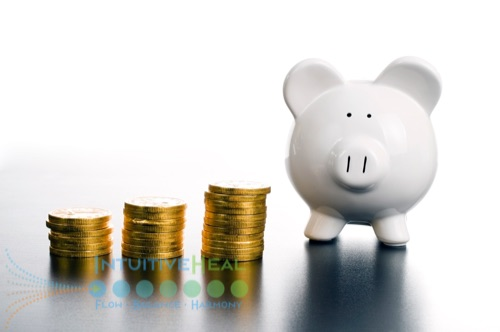 Photo of three stack of gold coins next to a white piggy bank