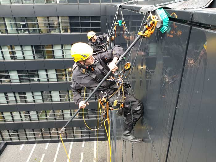 Industriekletterer reinigen seilgestützt Fassade / Fassadenreinigung durch Höhenarbeiter