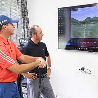Two golf pros watching a video
