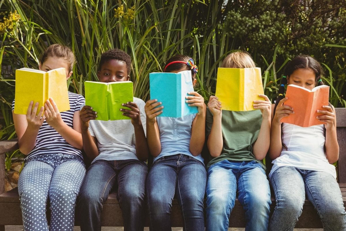 Kids sitting down in a row reading
