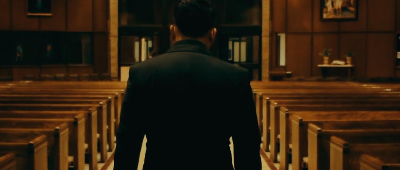 a man walking down a church aisle back facing
