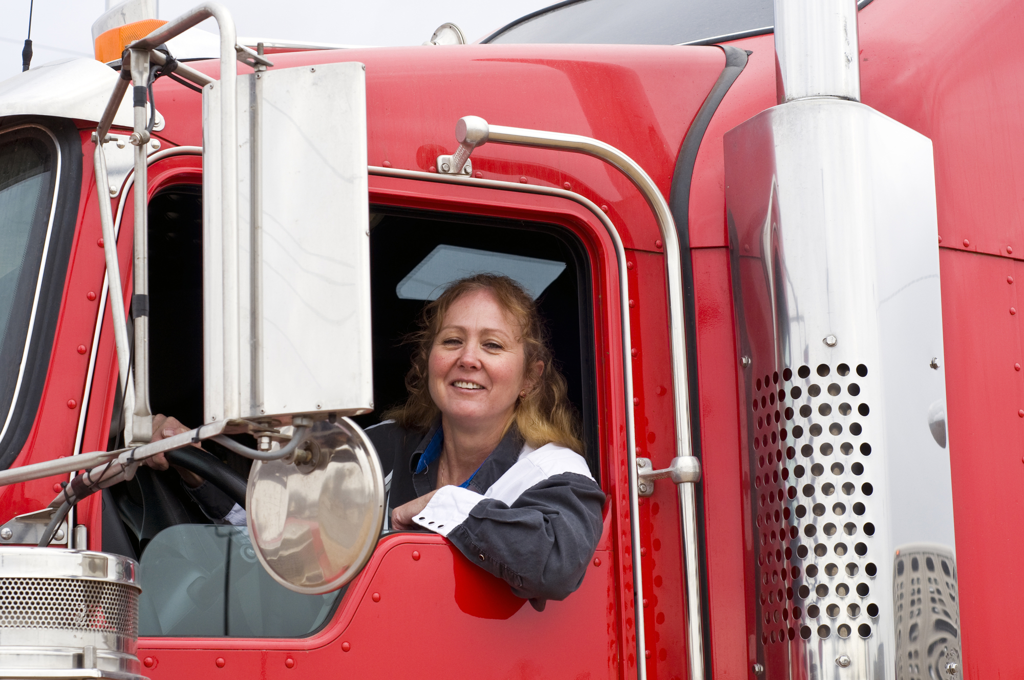 A woman behind the wheel of a long haul truck