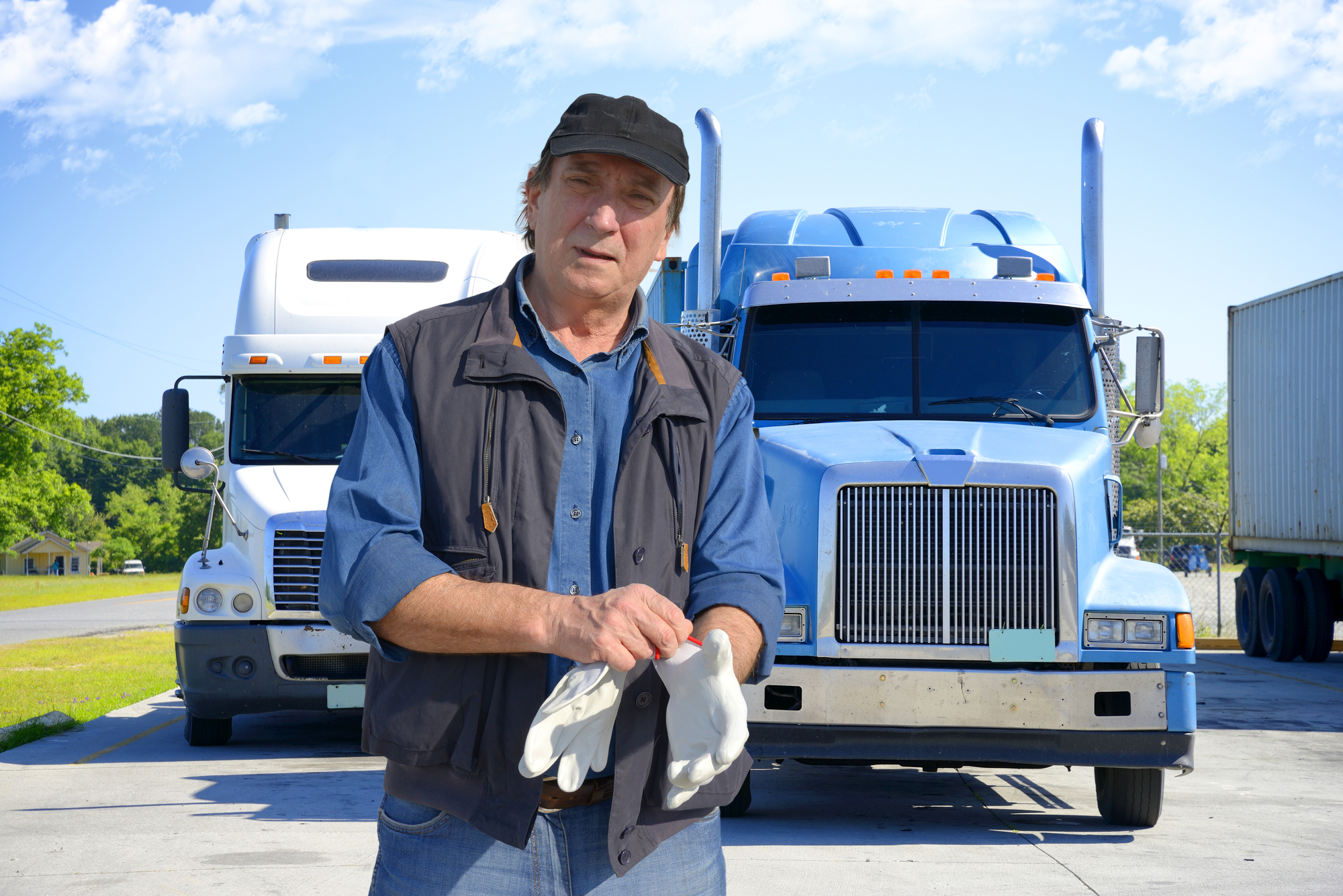 A truck driver standing in front of two semi trucks