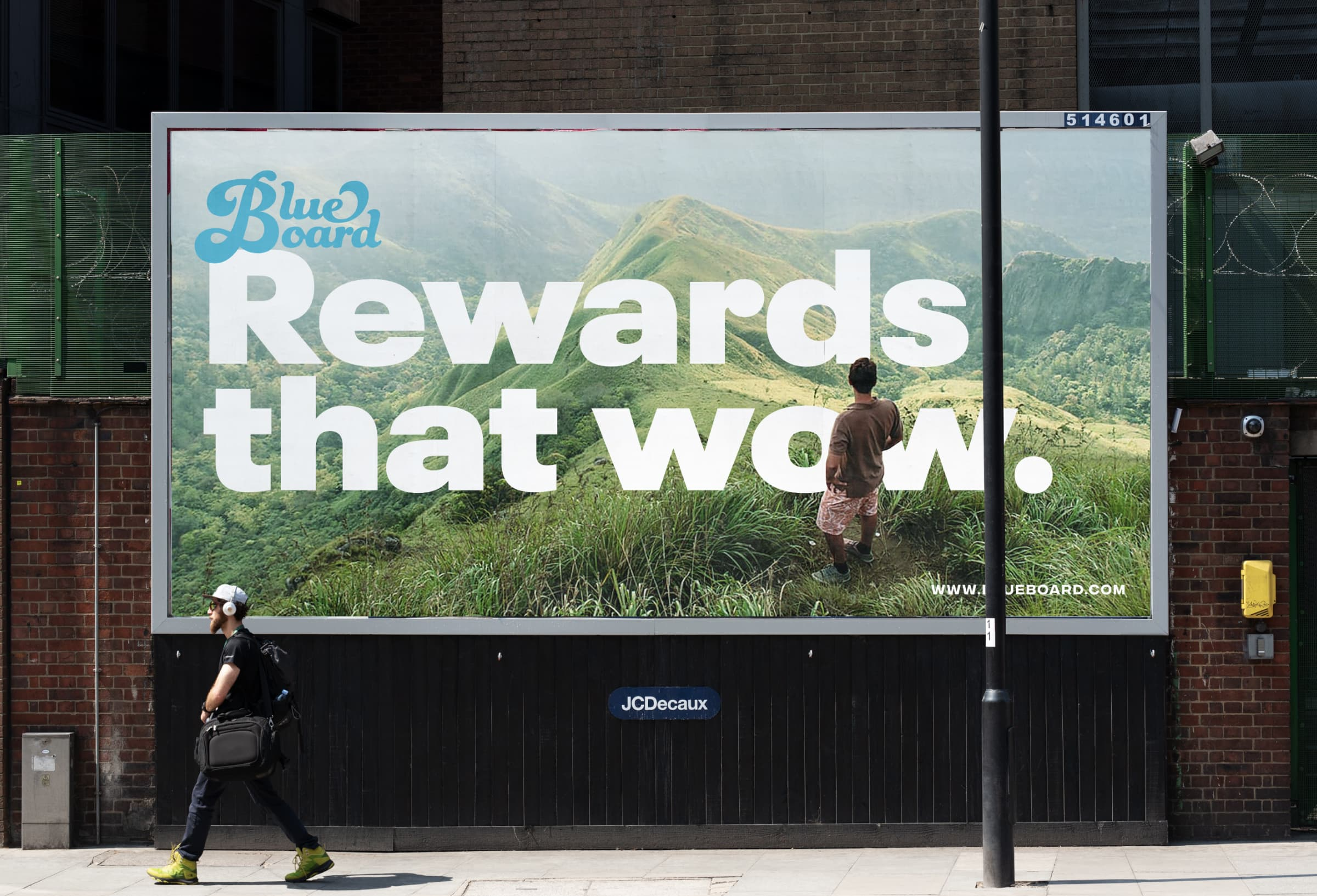 "An image of an out-of-home billboard ad featuring a man standing on top of a mountain range and the headline ""Rewards that Wow."""