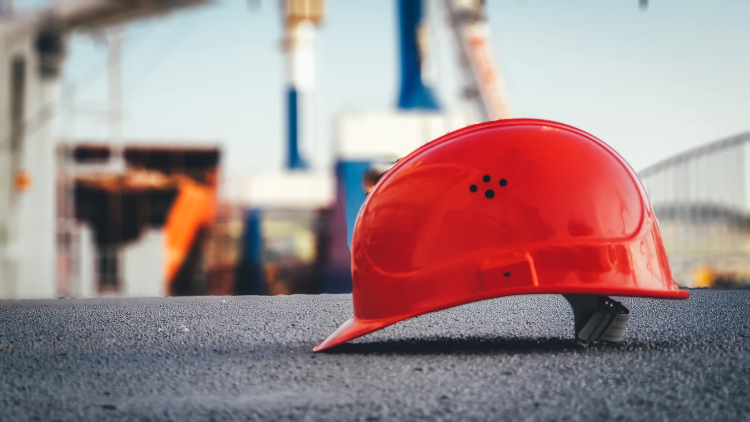 Red construction hat on floor of construction site