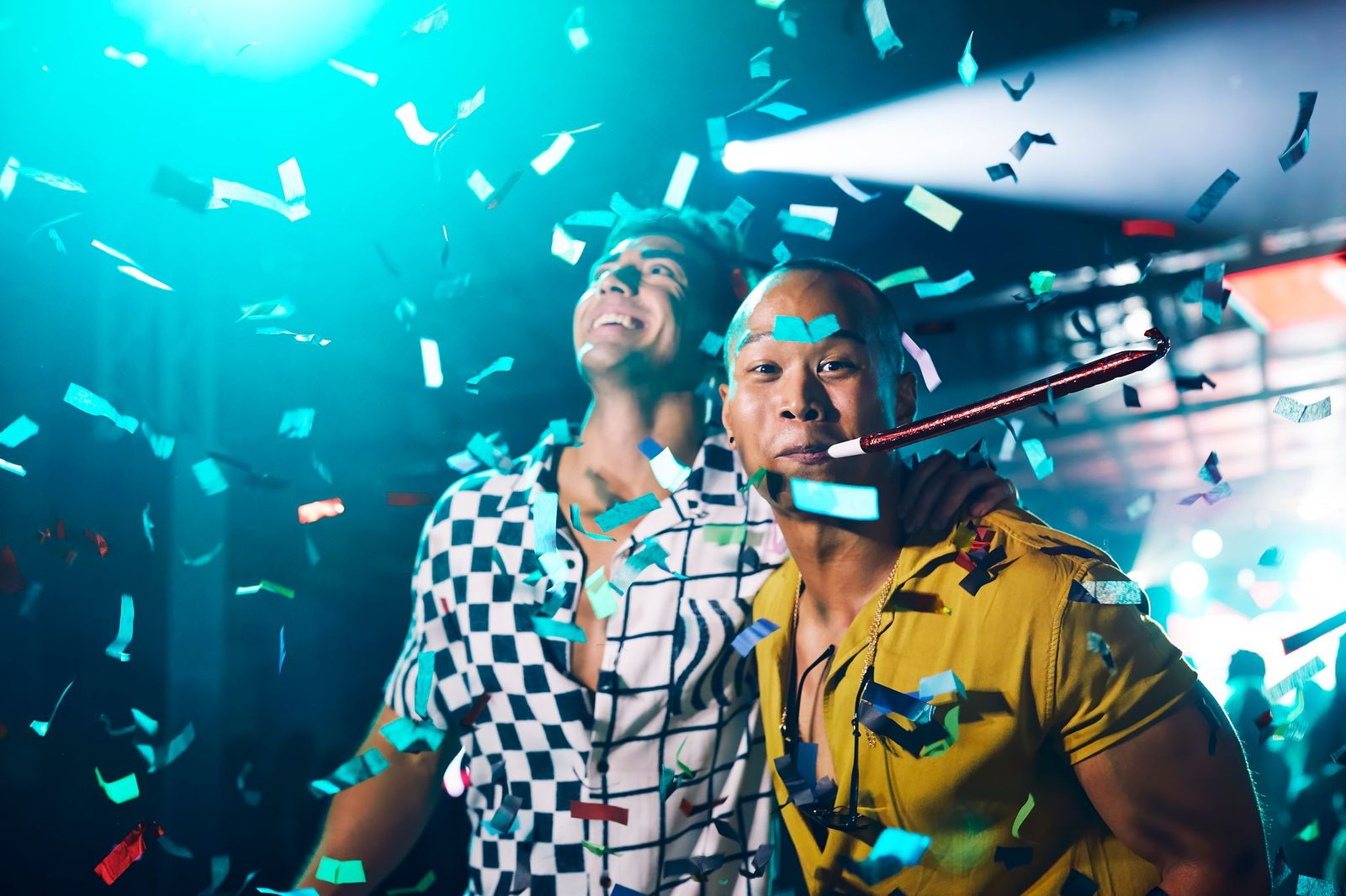 2 men at party with confetti and noise blowers