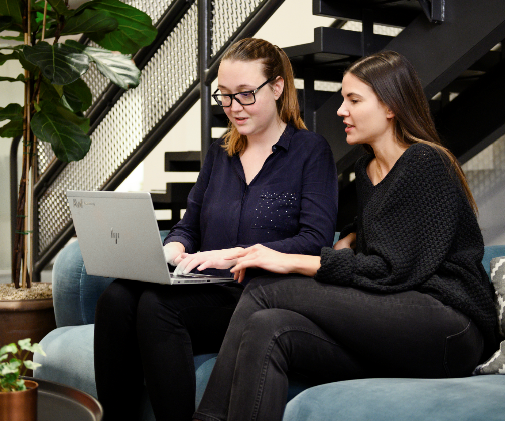 Two female coworkers with laptops working together in the lounge area at Bombayworks Stockholm office