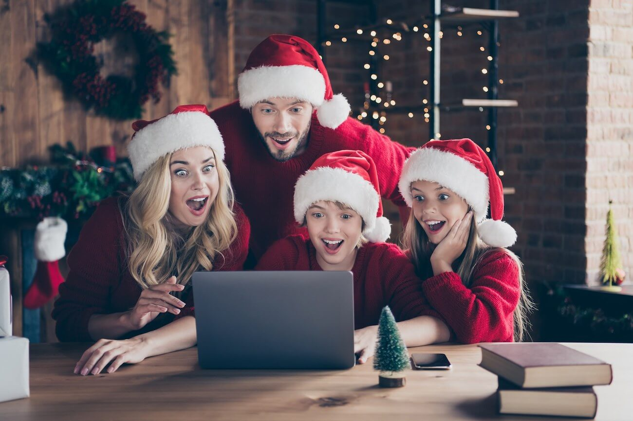 Family in Santa hats looking excited at a laptop screen