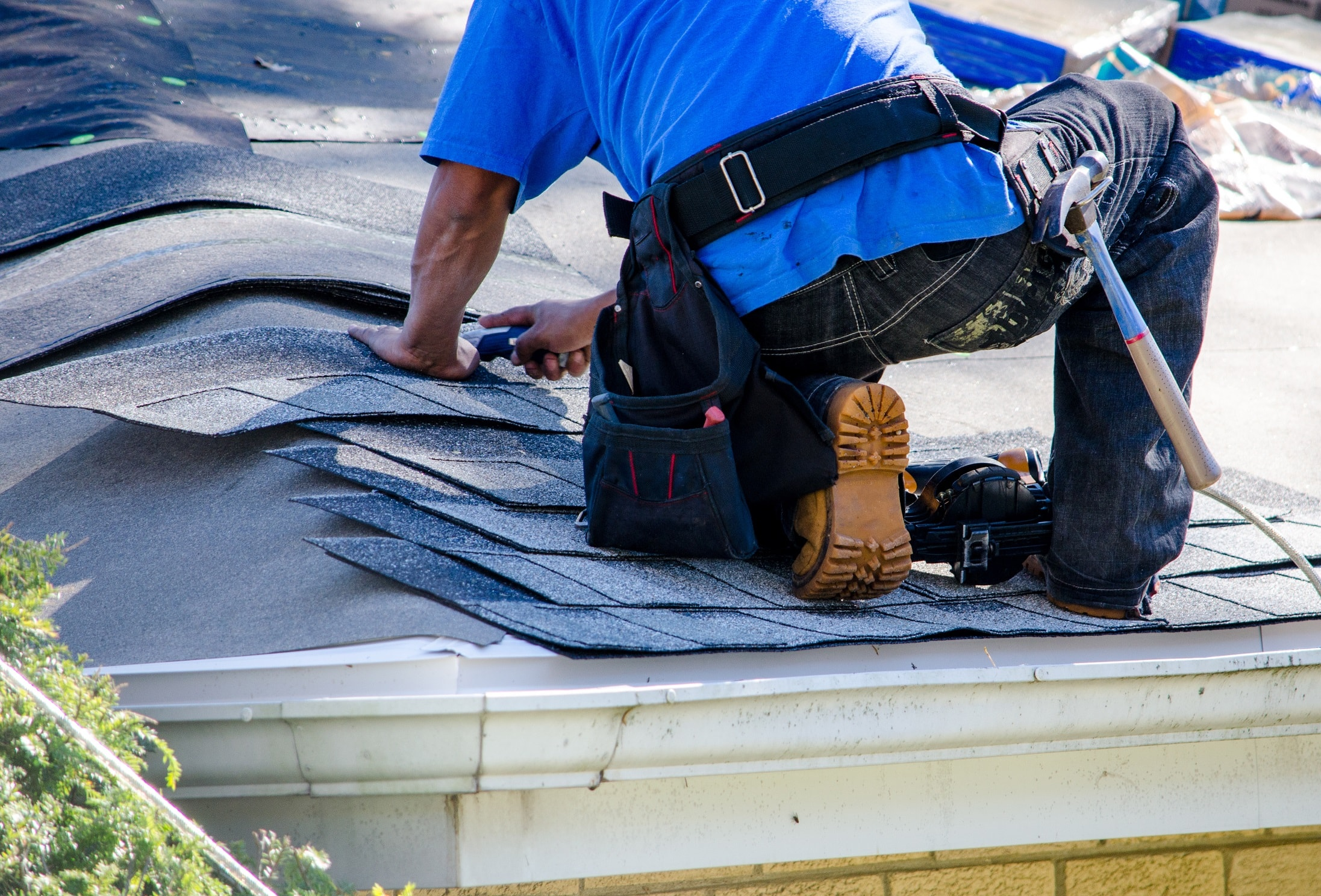 roofer cutting tiles with work boots on