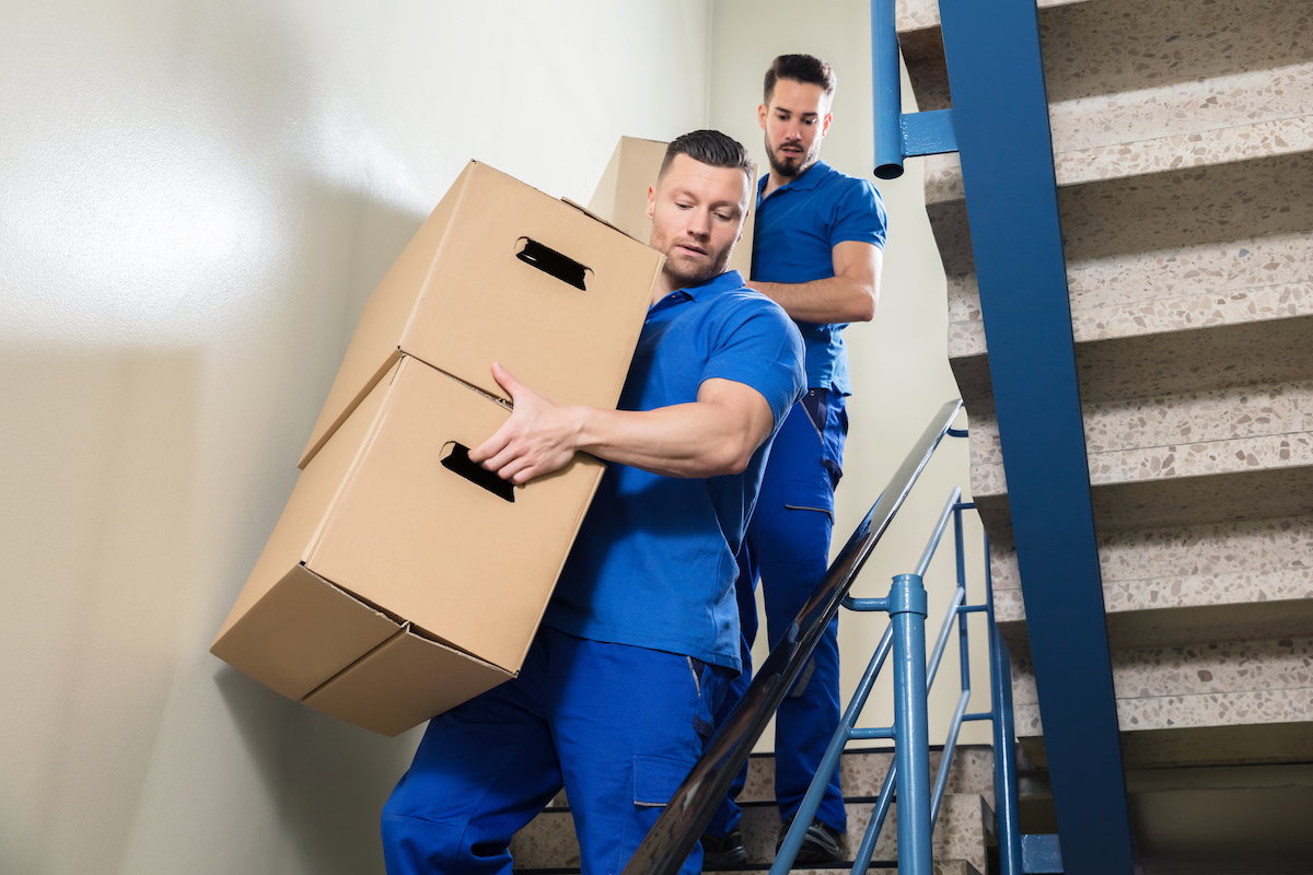 two men holding boxes while walking down stairs