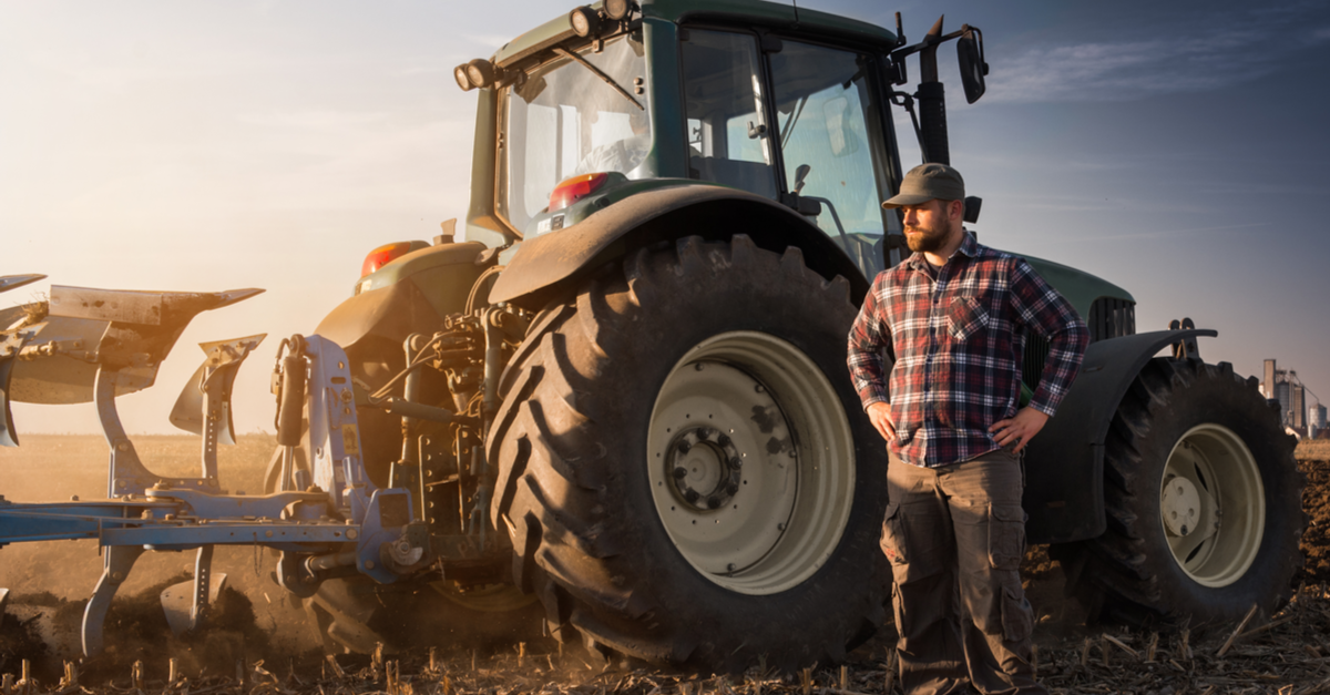 man in plaid standing in front of tractor
