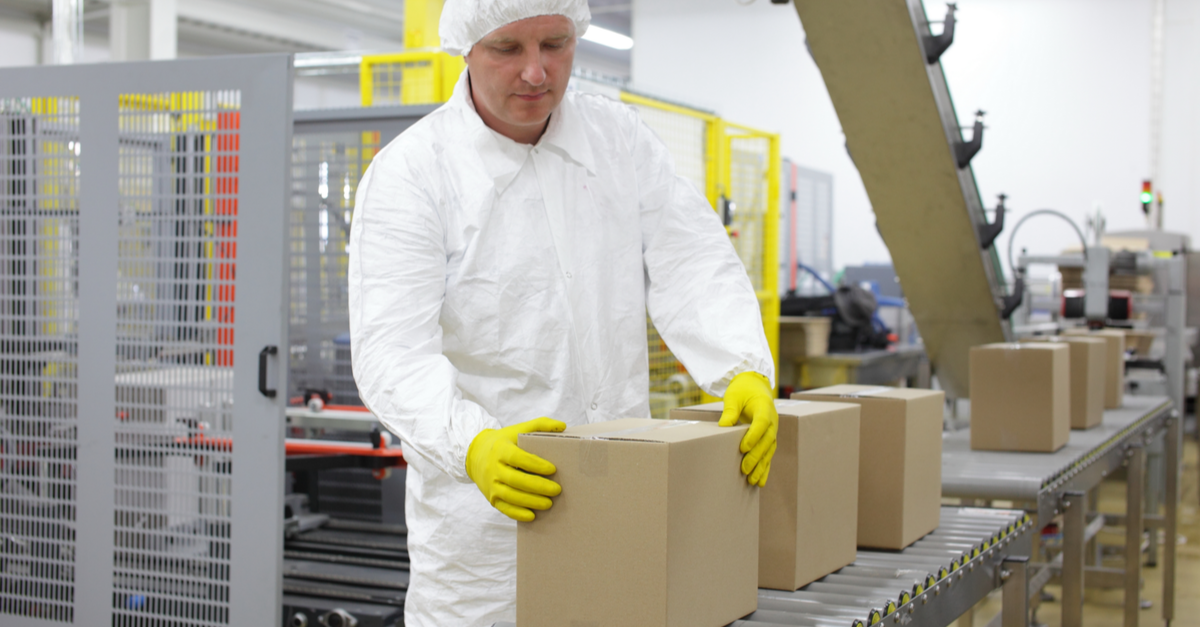 man in white with yellow gloves holding box in factory