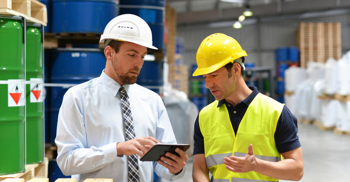 two men in hardhats looking at tablet