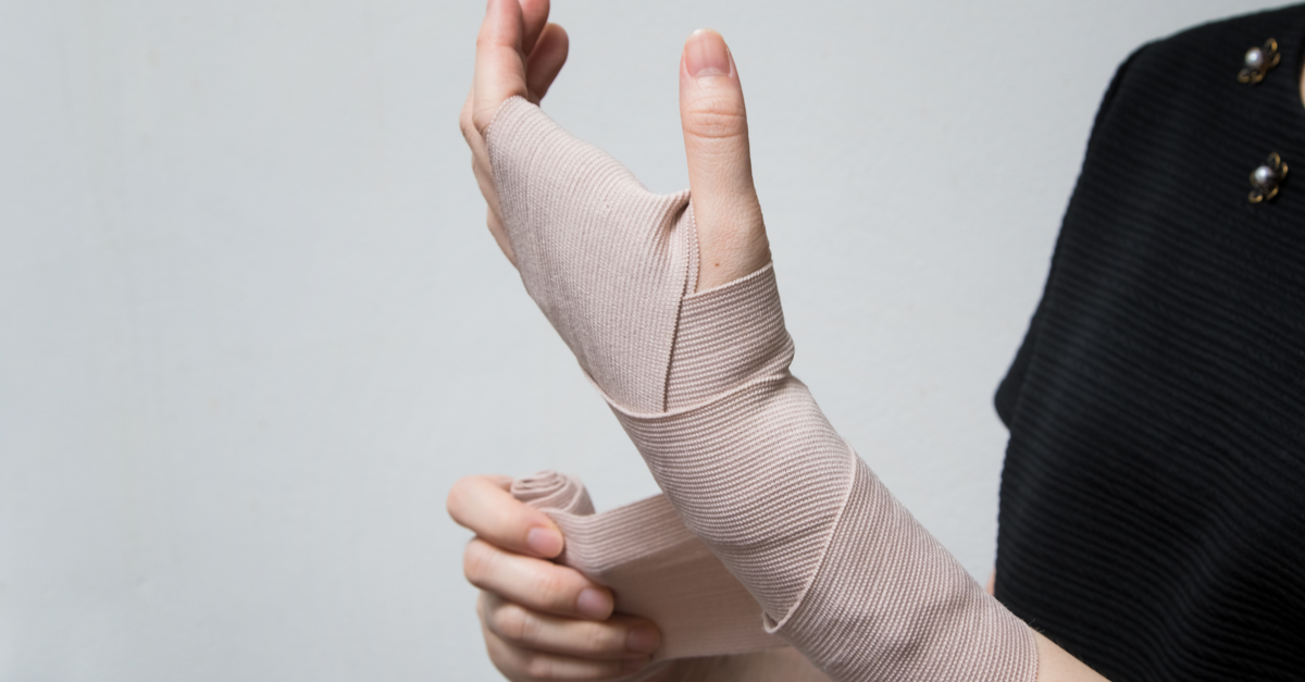 person wrapping their wrist with gauze