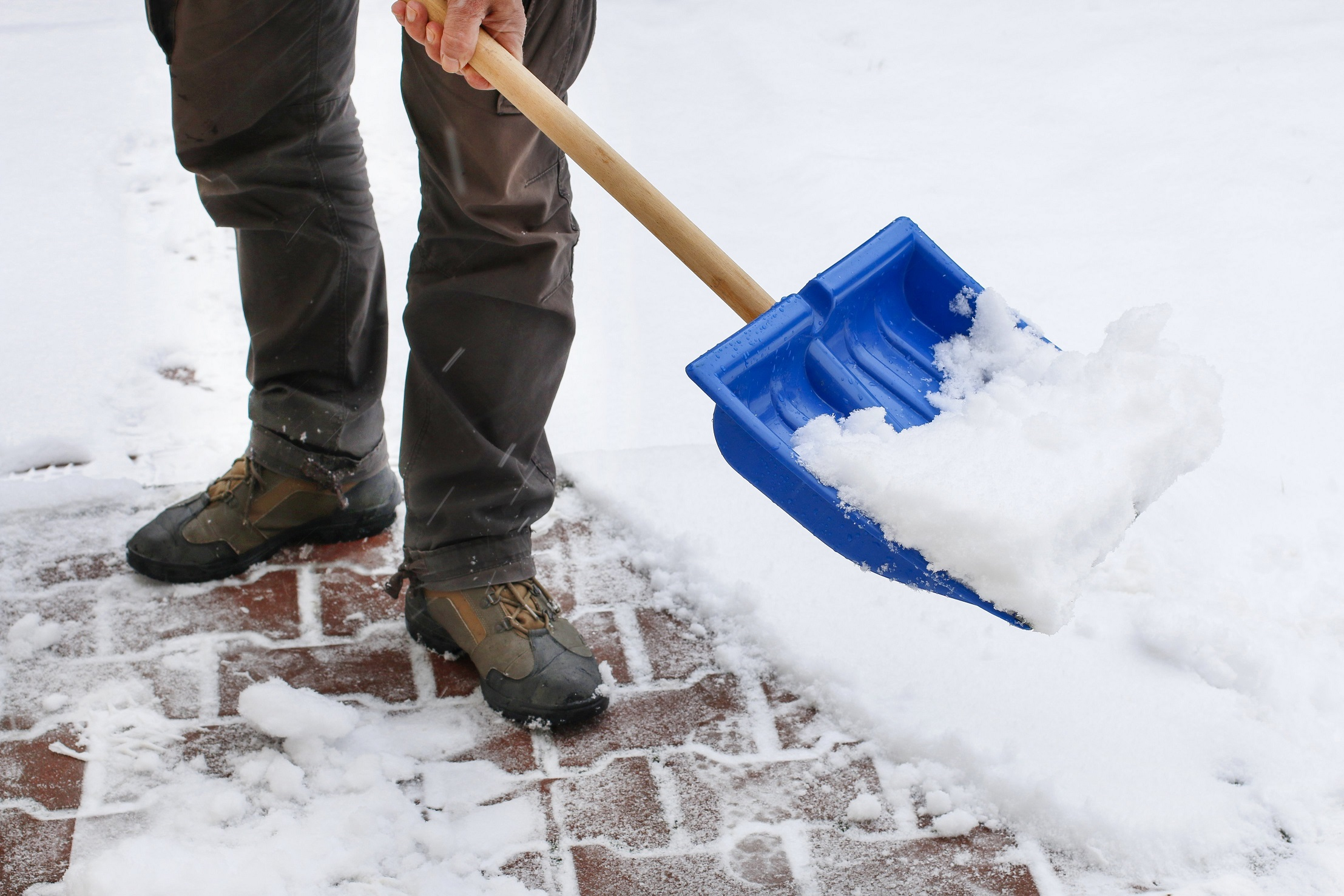 Man shoveling with a blue shovel