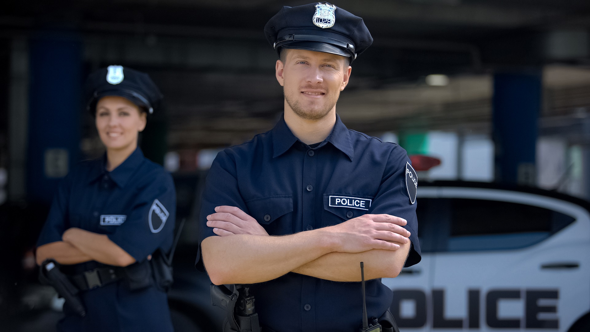 male police officer with female police officer in the back