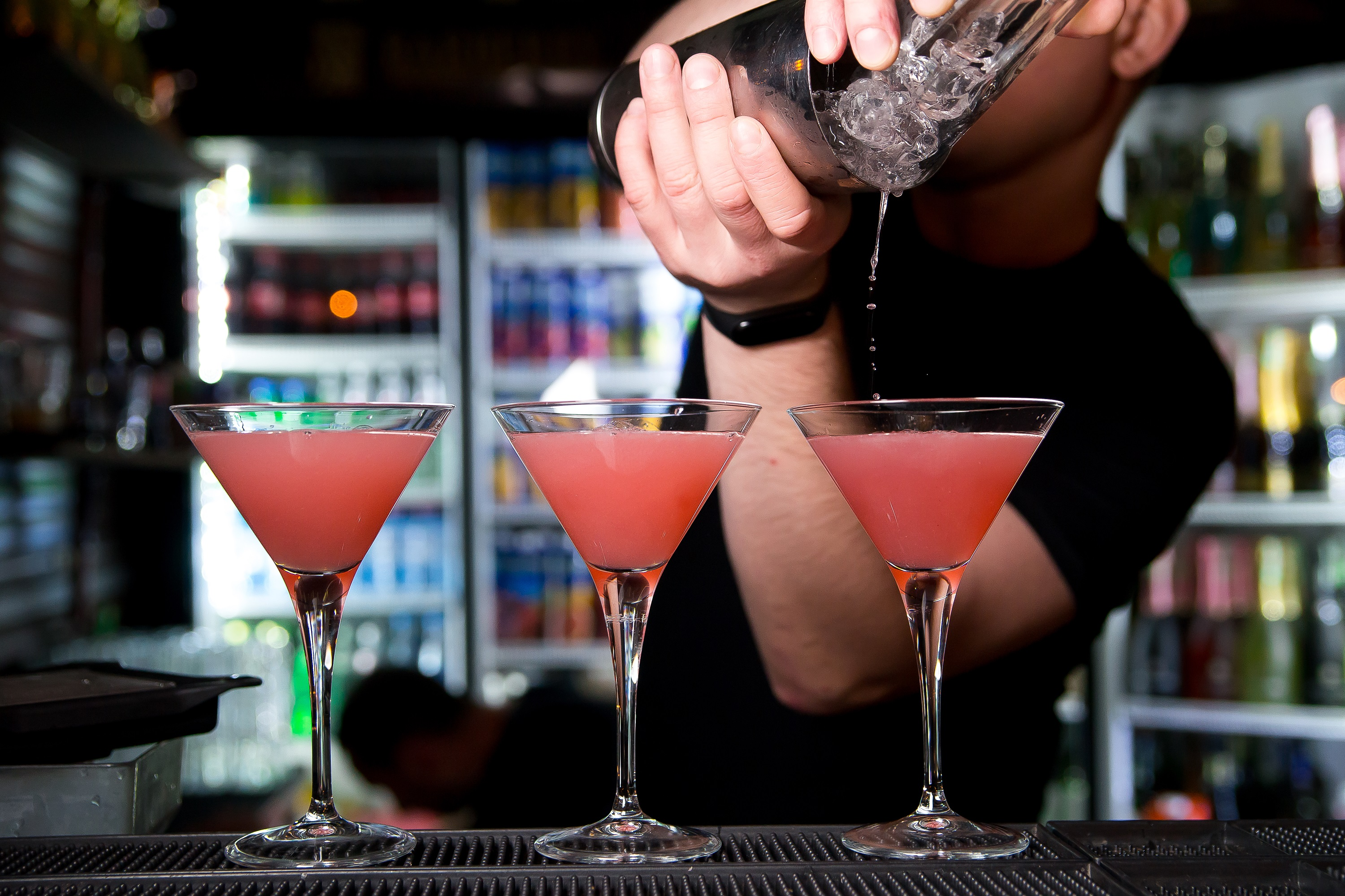 Bartender pouring 3 pink cosmo drinks