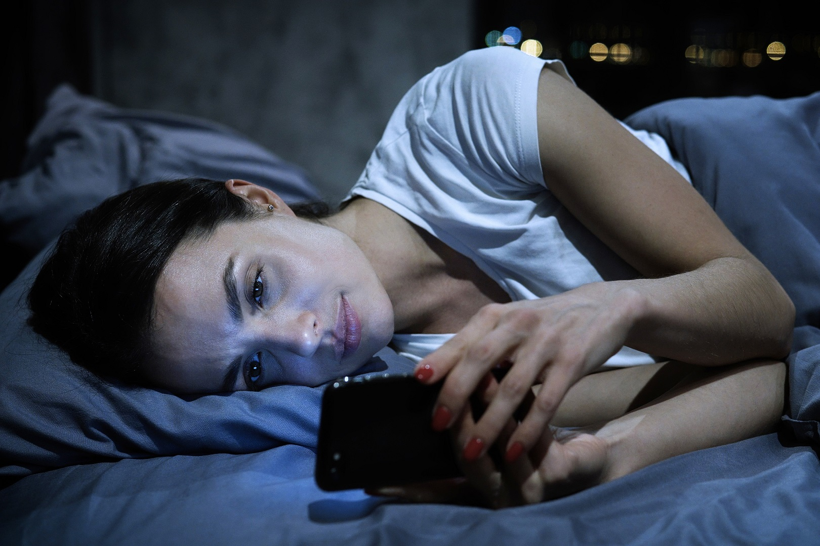 girl in bed on her phone