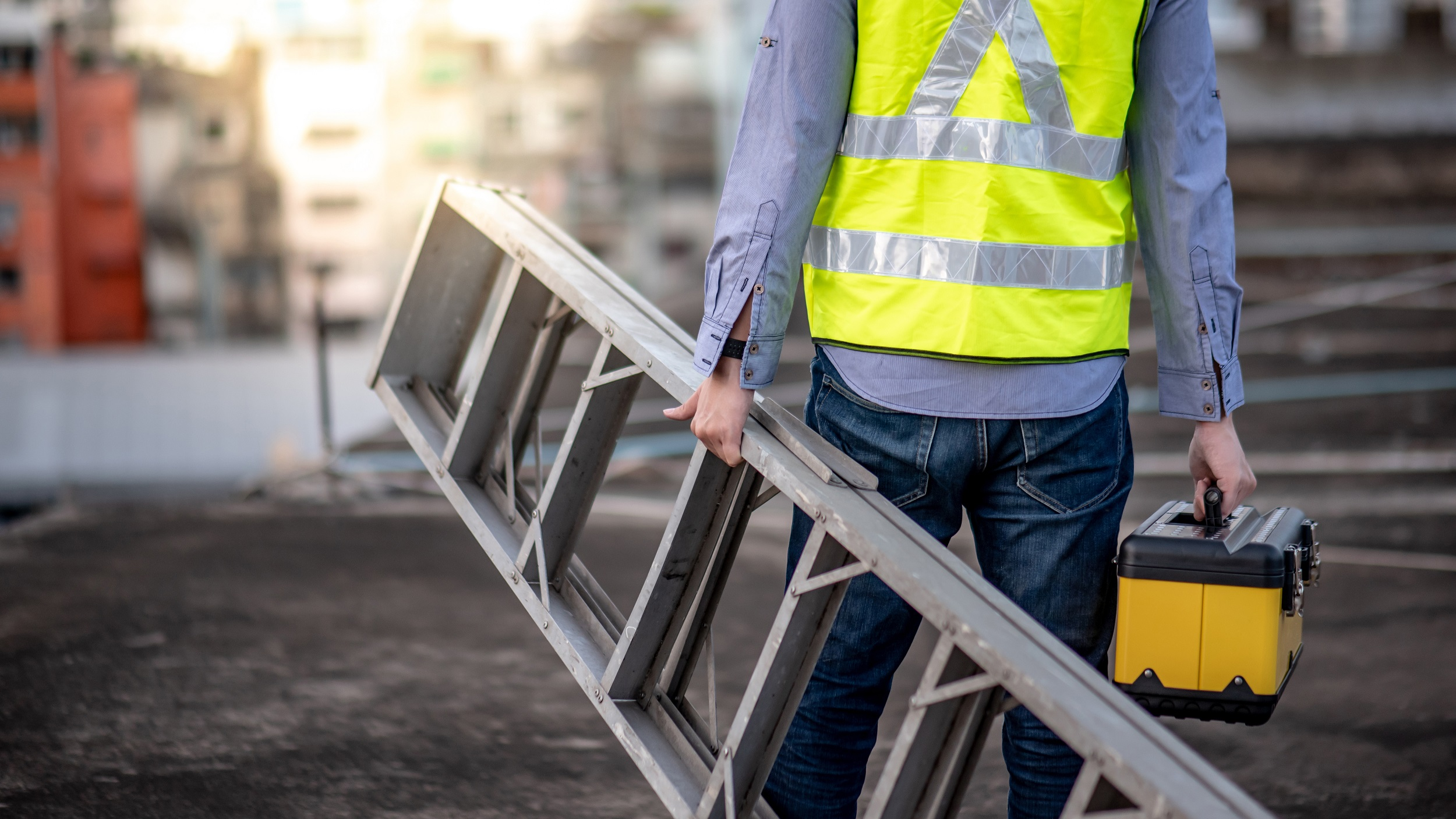 worker in reflective jacket holding ladder