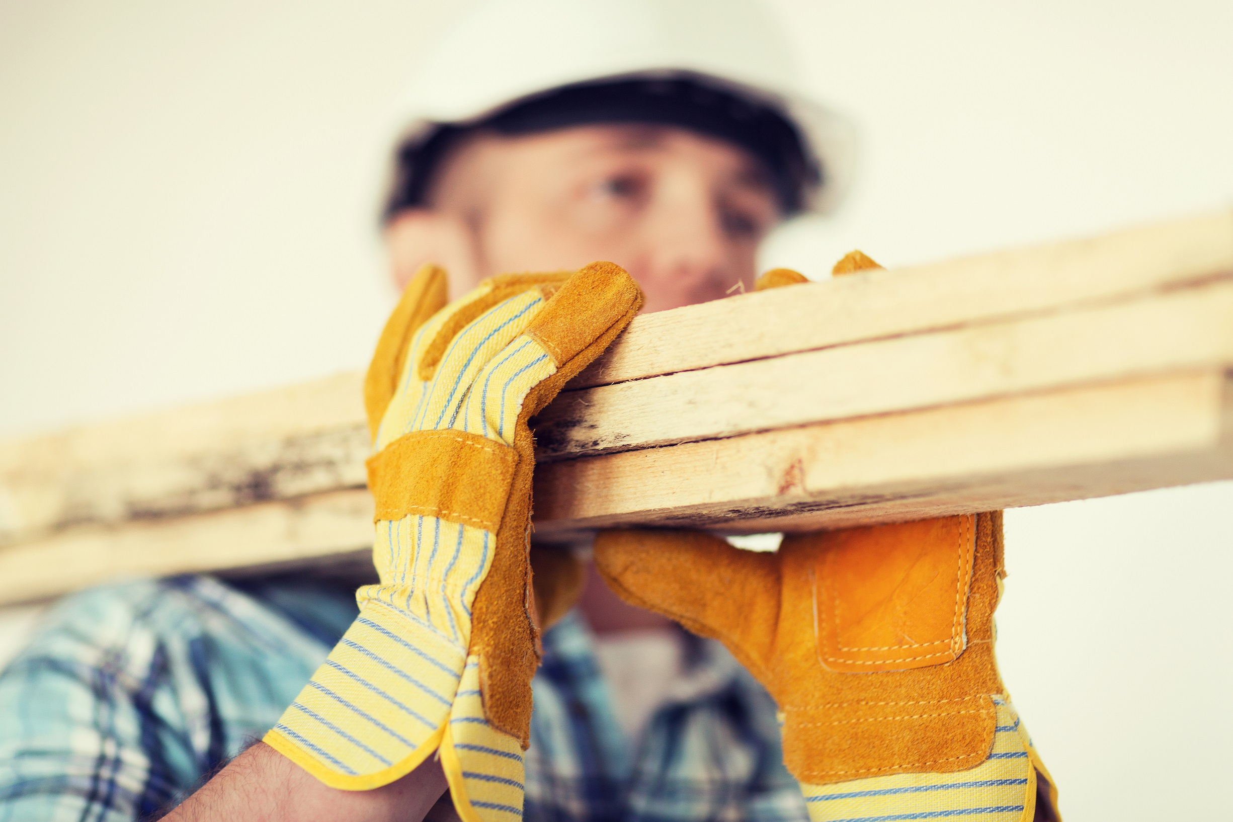 Construction worker holding wood with gloves on