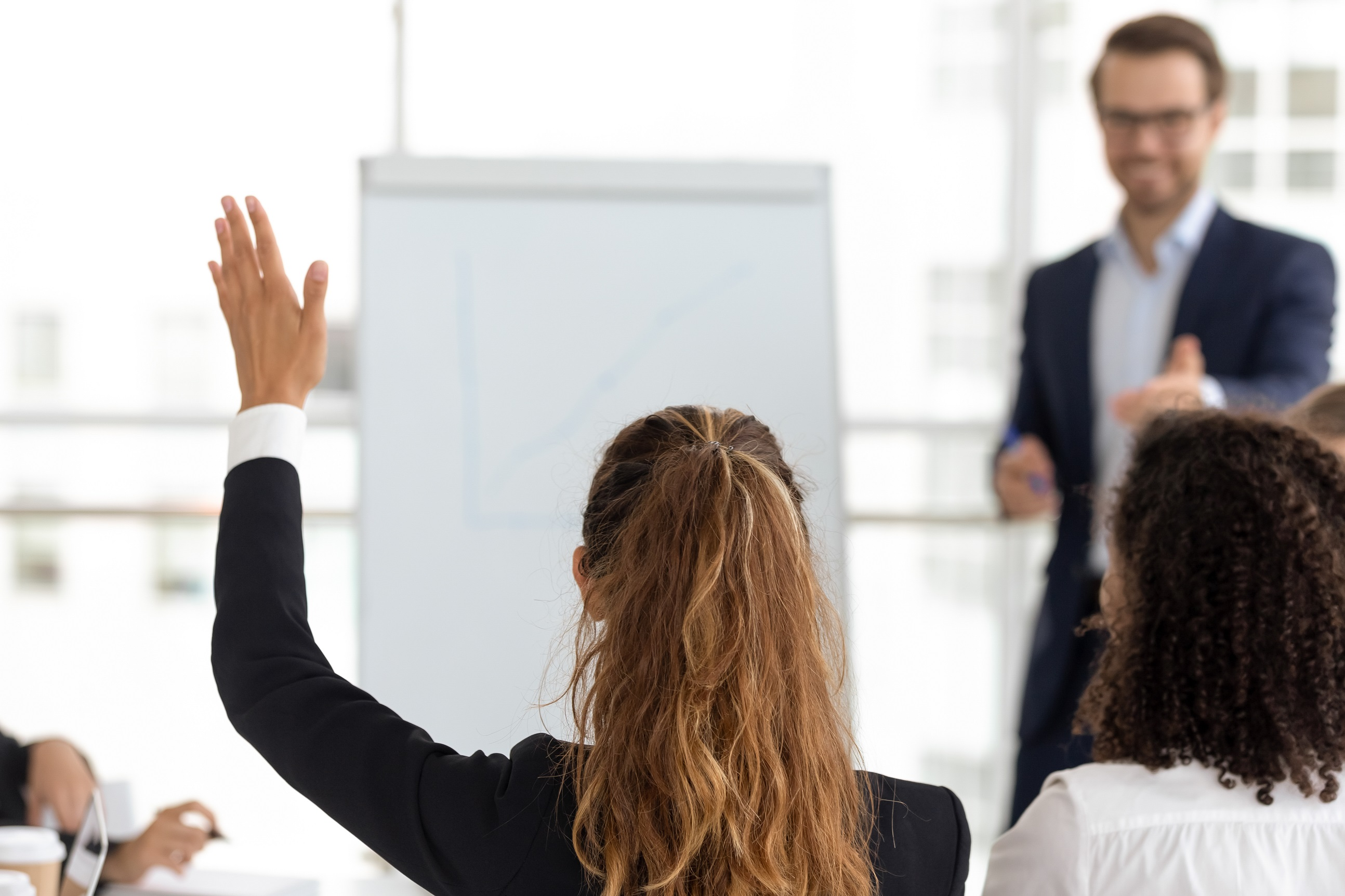 woman raising hand at a work meeting