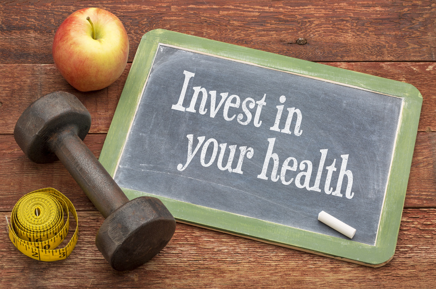 invest in your health on chalkboard next to an apple and dumbell