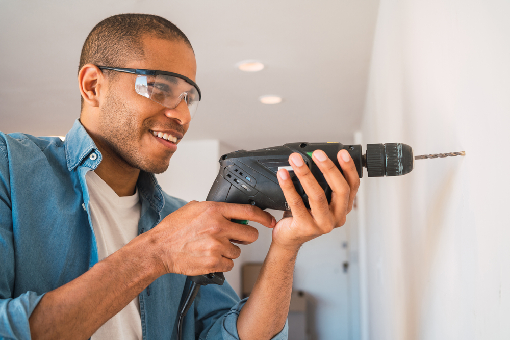 man using drill with safety glasses on
