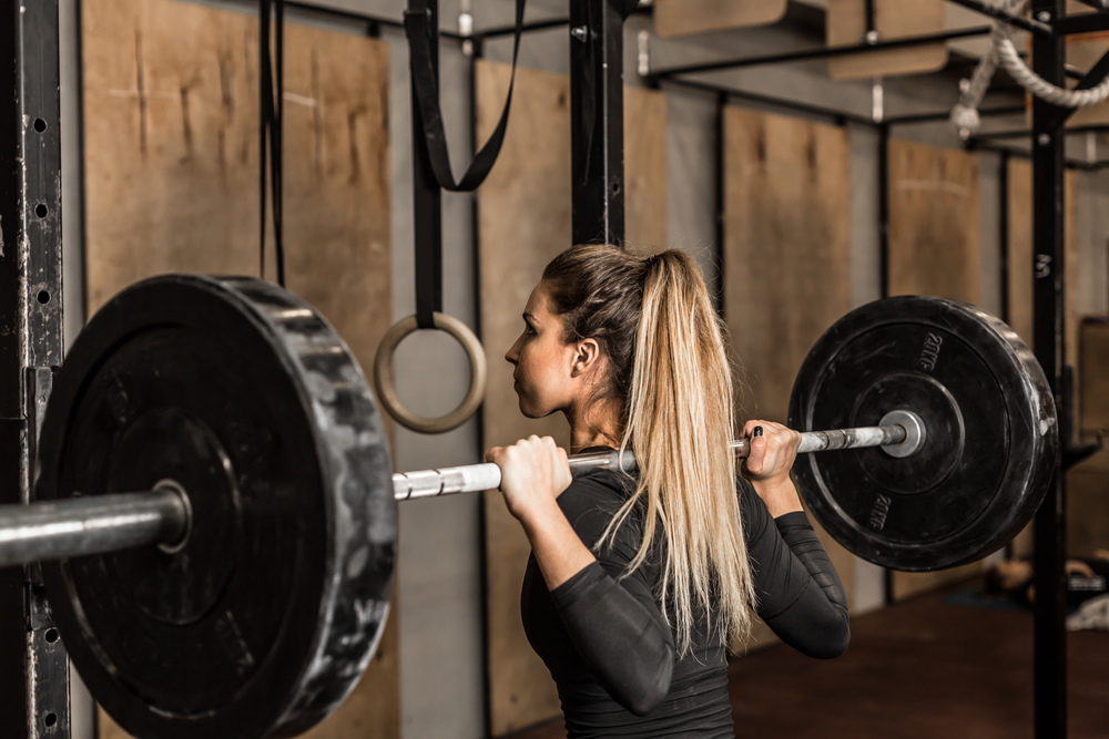 Back view young adult girl doing heavy duty squat in gym with barbell