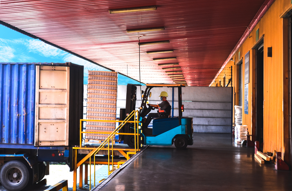 Forklift stuffing-unstuffing pallets of cargo to container on warehouse leveler dock