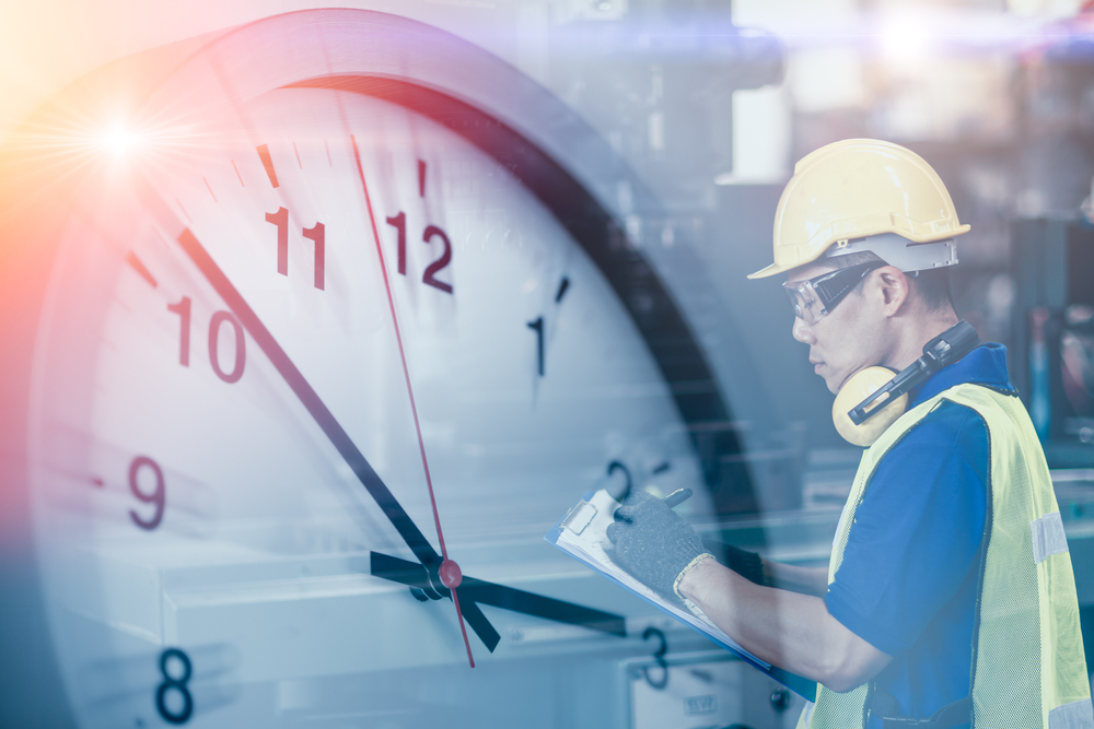 worker in front of large clock on clipboard