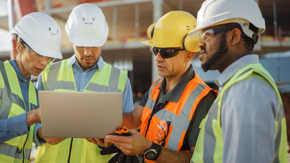 Diverse Team of Specialists Use Laptop Computer on Construction Site