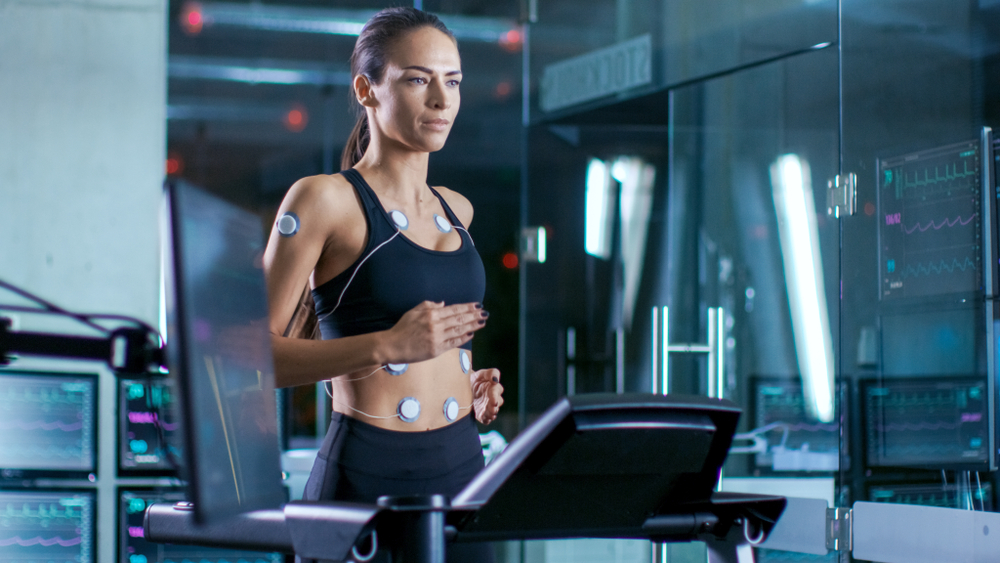 Woman Athlete Runs on a Treadmill with Electrodes Attached to Her Body