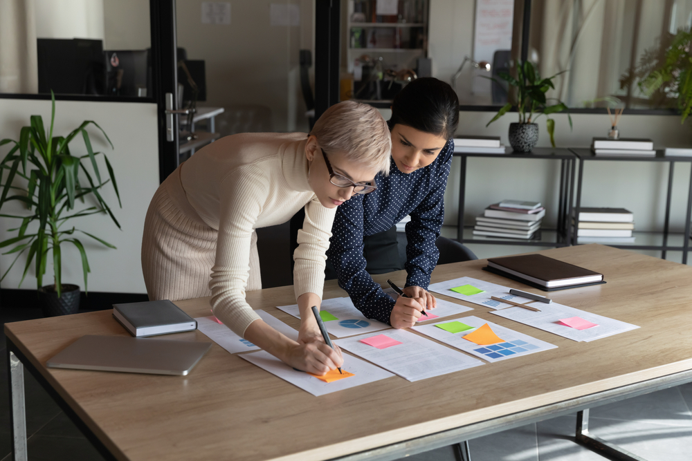 Focused young indian employee managing working processes with smart skilled 30s blonde female boss