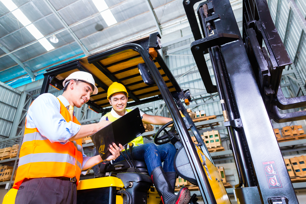 Asian fork lift truck driver discussing checklist with foreman