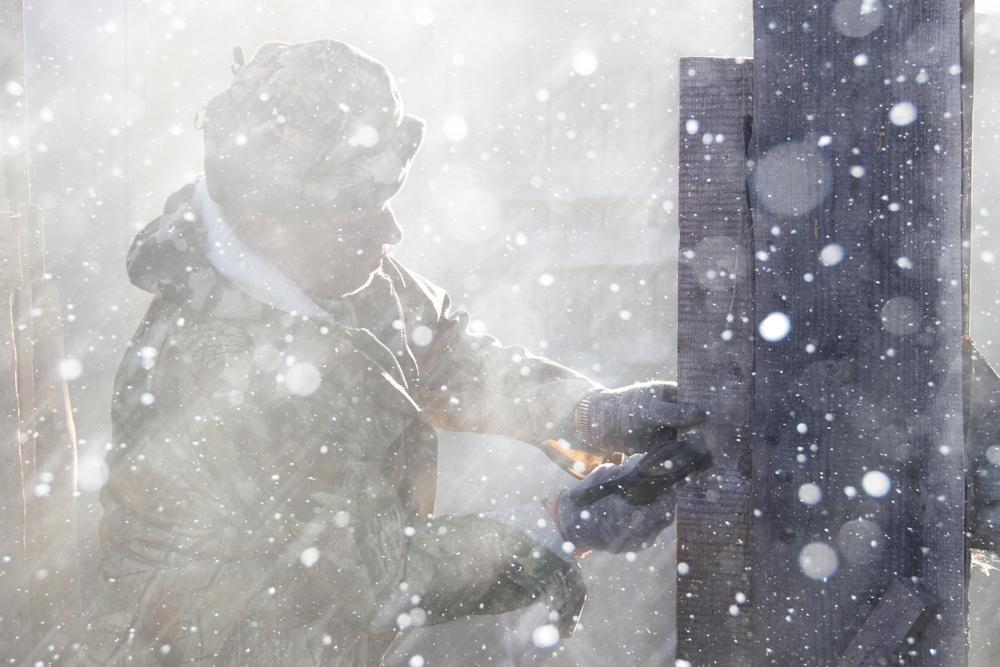 Man carpenter repair facility outside in a snowstorm