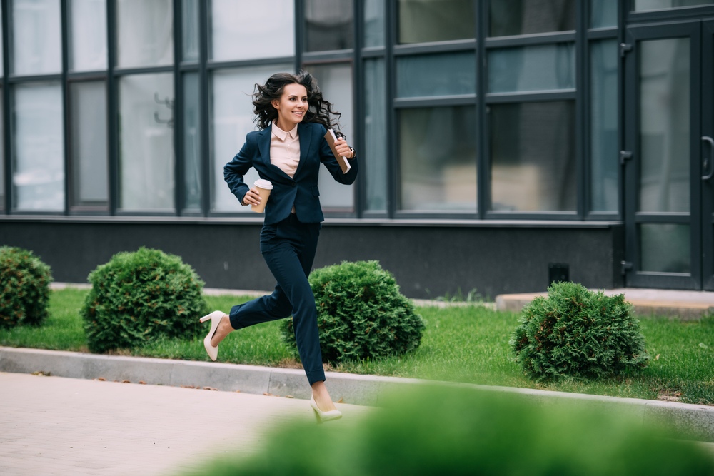 young happy businesswoman running to work with coffee and notebook