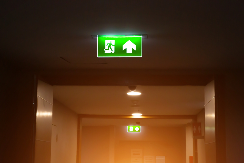 Green emergency fire exit sign or fire escape with the doorway