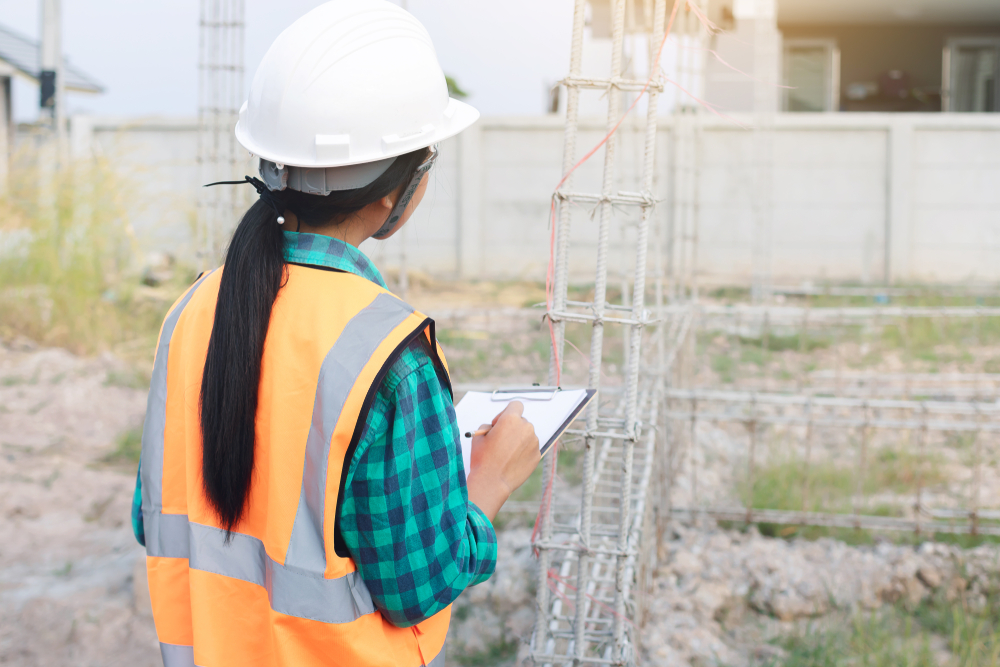 Female architects inspecting house construction workers